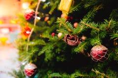 Unscharfe Zusammenfassung des Weihnachtsbaums verziert mit hängende Flitterball-, heller und kleinergeschenkbox stockfotografie