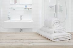 Unscharfer Badezimmerinnenhintergrund und weiße Badekurorttücher auf Holz Stockfotografie