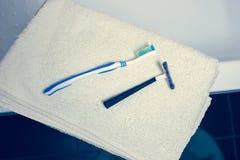Unscharfer Badezimmerinnenhintergrund und weiße Badekurorttücher auf Marmorzahnbürstenrasiermesser stockbild