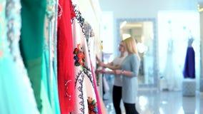 Unscharfer Berater und Käufer auf der Hintergrundauswahl das Kleid im Frauen ` s Bekleidungsgeschäft stock video