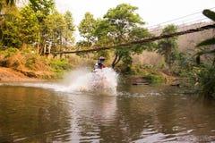 Unscharfer Bild enduro Motorradrennläufer fuhr in das Wasser lizenzfreie stockbilder