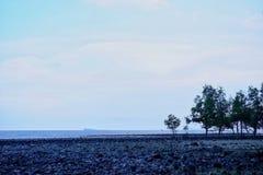 Unscharfer blauer Himmel kürzlich am Abend mit Steinstrand e lizenzfreies stockfoto