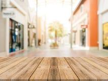 Unscharfer Einkaufszentrumhintergrund des hölzernen Brettes leere Tabelle Braune Holztischunschärfe der Perspektive im Kaufhaushi Stockfotografie