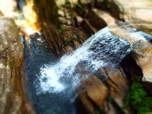 Unscharfer felsiger Wasserfall im Wald lizenzfreies stockfoto