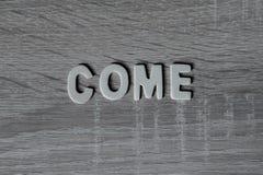 Unscharfer Hintergrund Buchstaben auf Holztisch ` Kommen ` stockfoto