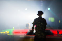 Unscharfer Hintergrund: Schlagen Sie, Disco DJ spielende und mischende Musik für Menge von glücklichen Menschen mit einer Keule N Stockfotografie