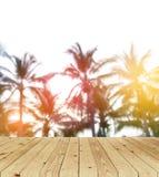 Unscharfer Hintergrund, Sonnenaufgang am Kokosnussbaum mit Holzfußboden Stockbilder