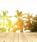 Unscharfer Hintergrund, Sonnenaufgang am Kokosnussbaum mit Holzfußboden Lizenzfreies Stockbild