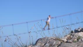 Unscharfer Mann, der auf das Seil auf langer hängender Brücke über dem Abgrund auf dem Gras auf Vordergrund in der Zeitlupe geht stock video