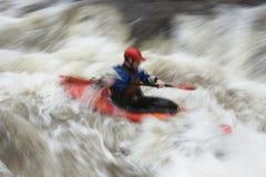 Unscharfer Mann, der im Fluss Kayak fährt Stockbilder