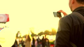 Unscharfer Mann, der Video im Freien mit seinem Handy notiert 4K Schuss, gelber Hintergrund stock video