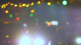 Unscharfer Schuss von den Autos, die langsam Nachtmehrfarbigen Lichthintergrund weitergehen stock video