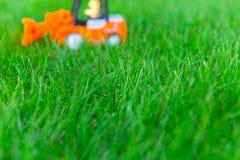 Unscharfer Spielzeuglader, LKW auf frischem gr?nem Gras, Spielzeug f?r Kinder lizenzfreies stockfoto