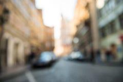 Unscharfer Stadtstraßenhintergrund mit Autos und Shops Stockbilder