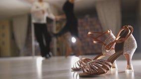 Unscharfer tanzender lateinischer Tanz der Professioneller und der Frau in den Kostümen im Studio, Ballsaalschuhe im Vordergrund lizenzfreies stockbild