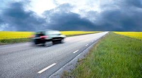 Unscharfes Auto auf dem Rapsgebiet Lizenzfreies Stockfoto