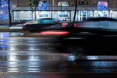Unscharfes Autoauf nasse Stadtstraße während des Regens schnell fahren Lizenzfreie Stockbilder