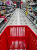 Unscharfes Bild einer Warenkorblaufkatze in einem Supermarktgang mit Regalen auf beiden Seiten Stockfotografie