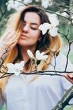 Unscharfes Bild eines hübschen Mädchens, das blühende Magnolienbäume genießt, lizenzfreies stockbild