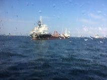Unscharfes Bild für Hintergrund des Tankers im Meer hinter nassem Gewinn Stockfotos