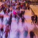 Unscharfes Foto vieler Leute, die auf die Eisbahn am Abend eislaufen, setzen draußen im Park auf Winter Zeit fest Weihnachten, Sp Stockbilder