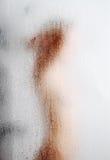 Unscharfes Schattenbild durch weinendes Glas Stockfotos
