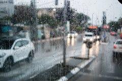 Unscharfes Straßenbild durch Autofenster mit Regentropfen Lizenzfreie Stockfotografie