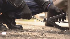 Man changing wheel on a car. Unscrew bolts on the wheel of the car stock footage