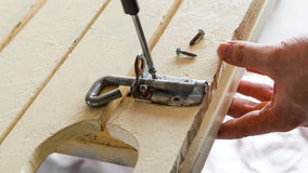Unscrewing Bolt. A man unscrewing a screw from a bolt lock on a wooden gate.  Screwdriver is still Stock Photography