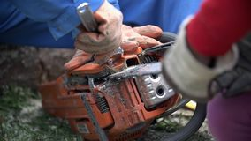 Unscrewing chainsaw close up. Man in blue working clothes and gloves unscrewing chain from chainsaw slow motion close up stock video