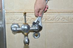 Unscrewing an old bathroom faucet stock image