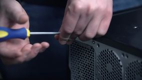 Unscrewing and removing screw from side cover of PC box. Removing screw from side cover of PC, slow motion screw falls down stock footage