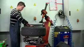 Unscrewing the screws on a tire. Auto mechanic unscrews old tires and replaces them with new ones stock video footage