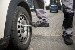 Unscrewing a tire with help of a feet Stock Image