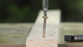 Unscrewing a wood screw with an electric screwdriver. Screw with star head is easily unscrewed stock video footage
