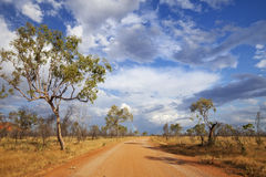 Unsealed road in the outback of Western Australia. An unsealed road through the Australian outback with a rainbow at the end of the road. Photographed in the Royalty Free Stock Image
