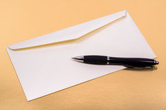Unsealed white envelope with a ballpoint pen on the side Stock Photos