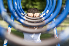 Unseen young girl in a playground on monkey rings Royalty Free Stock Image