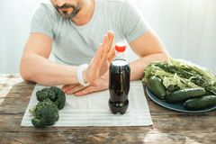Unshaken concentrated man gesticulating and sitting by the table. Bad idea. Unshaken concentrated decisive man refusing to drink cola gesticulating and sitting Stock Photography