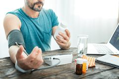 Unshaken concentrated man measuring pulse looking at the jar. Will be better. Unshaken concentrated occupied man sitting by the table measuring pulse looking at Royalty Free Stock Photo