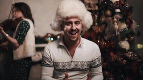 Musician in fur hat singing with string quartet sitting near christmas tree. Unshaved caucasian joyful musician in white fur hat singing with string quartet stock footage