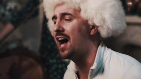 Unshaved singer in white fur hat singing with string quartet sitting in room. Unshaved caucasian joyful singer in white fur hat singing with string quartet stock footage