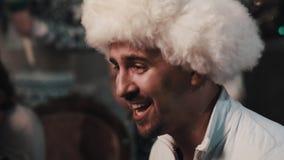 Unshaved vocalist in white fur hat singing with string quartet sitting in room. Unshaved caucasian joyful vocalist in white fur hat singing with string quartet stock footage