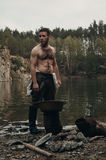 Unshaved gold digger standing near lake with rocky bank. Caucasian gold digger in retro clothes standing near lake after hard work. He wears shirt, leather pants stock images