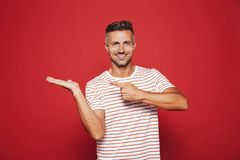 Unshaved guy in striped t-shirt gesturing index fingers at copyspace on his palm, isolated over red background. Unshaved guy in striped t-shirt gesturing index stock photos