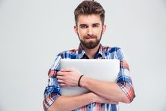 Unshaved handsome man holding laptop Royalty Free Stock Images