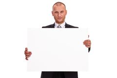 Unshaven businessman in a dark suit, holding a big sign, white c Stock Photo