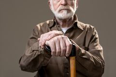Unshaven disabled pensioner with wooden stick Royalty Free Stock Image