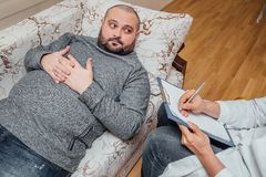 Unshaven fat man visits a psychologist. Psychologist writing notes. Unshaven fat men visits a psychologist. Psychologist writing notes Royalty Free Stock Image