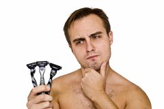 Unshaven guy with three razors Royalty Free Stock Photos